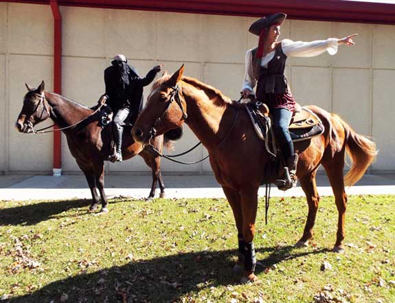 Two students riding horses on the college campus, wearing pirate Halloween costumes
